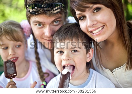 Happy family and group children eat ice cream. Outdoor. - stock photo