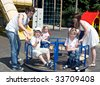 Happy family and three children in park on carousel. - stock photo