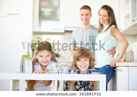 Happy family and two children in kitchen with fresh lime water - stock photo