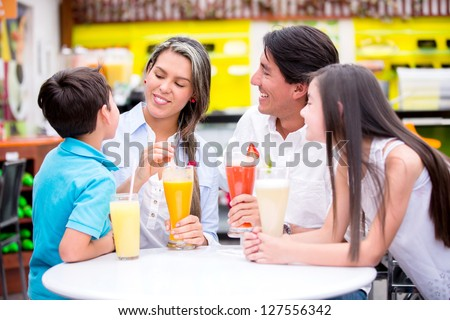 Happy family at a cafeteria drinking juices - stock photo