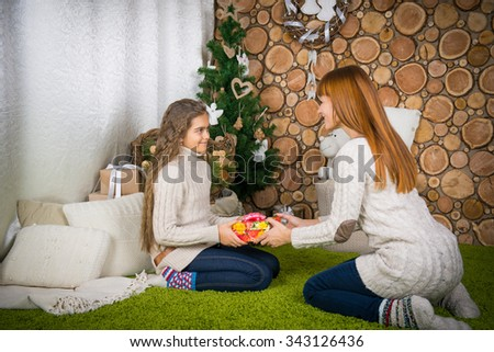 happy family at Christmas. mother and child daughter give gifts - stock photo