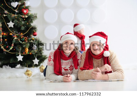 Happy family at Christmas. Parents are on the floor and smiling. Kid in the background. In public, the red caps of Santa. In the background stands and Christmas tree ornaments. - stock photo