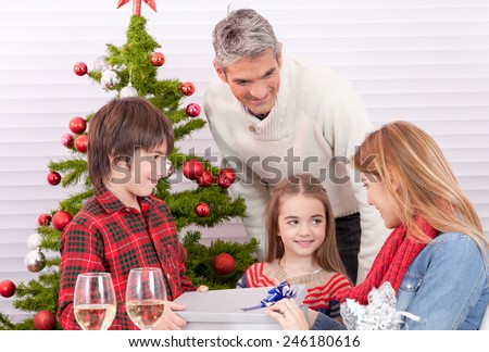 Happy family at Christmas table giving presents each other. - stock photo