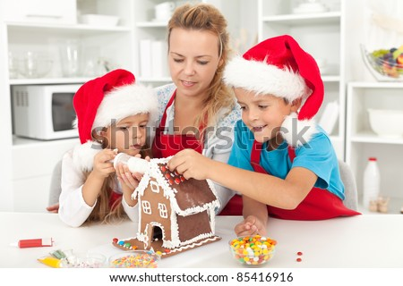 Happy family at christmas time decorating a gingerbread house in the kitchen