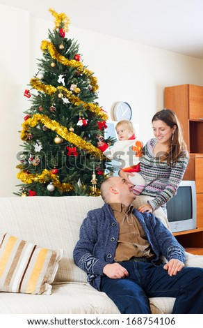Happy family at Christmas time  on sofa at home