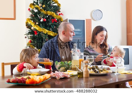 Happy family at Christmas time or winter holiday season around festive table at home