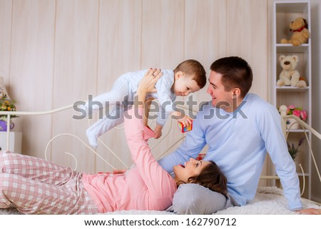 happy family at home in their pajamas on the bed