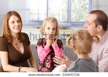 Happy family at home, little girl in tiara in the focus, pregnant mother, father and little sister around her. - stock photo