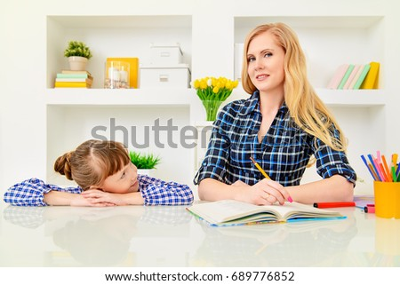 Happy family at home. Mother and daughter read and do lessons together. Education.