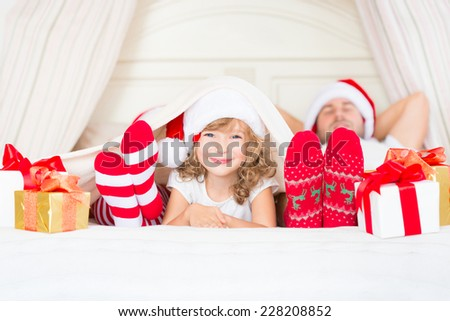 Happy family at home. Mother, father and child lying in the bed with Christmas gift. Winter holiday concept - stock photo
