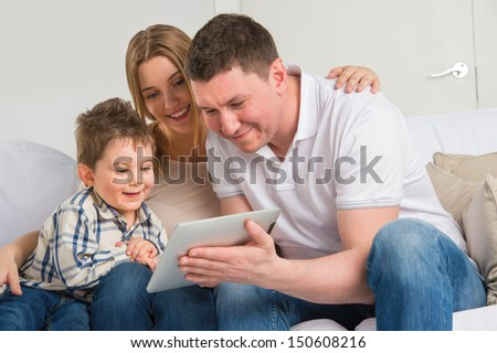 Happy family at home using electronic tablet to play together - stock photo