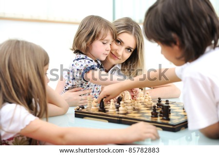 Happy family at home, young mother playing chess with her children - stock photo