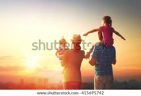 happy family at sunset. father, mother and two children daughters having fun and playing in nature. the child sits on the shoulders of his father. - stock photo
