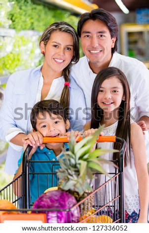 Happy family at the supermarket with a shopping cart
