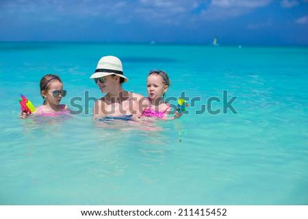 Happy family at tropical beach having fun - stock photo