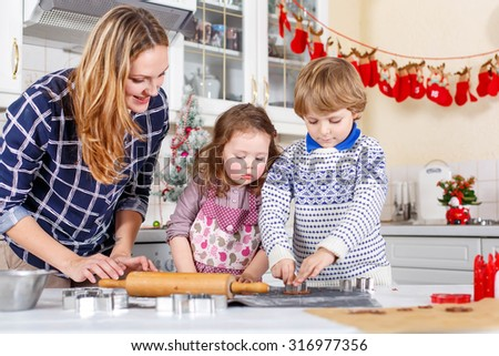 Happy family baking Christmas cookies at home. Little brother, sister and mother having fun in domestic decorated kitchen. Traditional leisure with kids on Xmas - stock photo