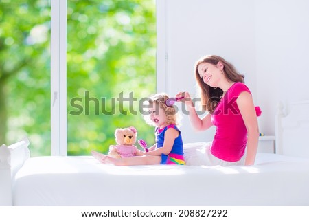 Happy family, beautiful young mother and her adorable little daughter, cute funny girl with curly hair brushing hair and playing with a teddy bear toy in a sunny white bedroom with window - stock photo