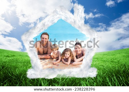 Happy family beside the swimming pool against green field under blue sky - stock photo