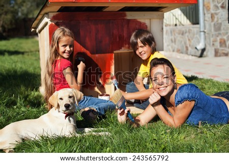Happy family building a doghouse for their little labrador puppy - painting - stock photo