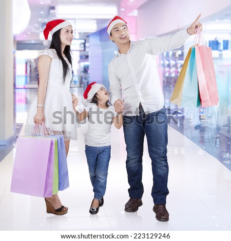 Happy family carrying shopping bags and looking at a store in the mall - stock photo