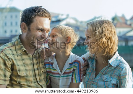 Happy family caucasian father mother and son at the street of old town in the evening sunshine have fun smiling and talking to each other.
