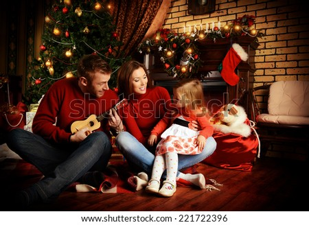 Happy family celebrating Christmas at home by the fireplace and the Christmas tree. - stock photo