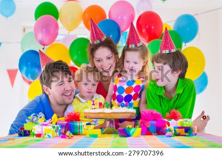 Happy family celebrating kids birthday. Parents and children celebrate together. Child party with balloon decoration, cake, candles and presents. Celebration for baby boy, toddler girl and school kid. - stock photo