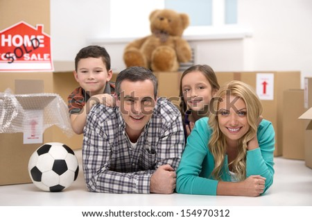 Happy family. Cheerful family lying together near the cardboard boxes and smiling  - stock photo