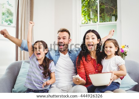 Happy family cheering while watching TV at home - stock photo
