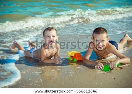 Happy family. Children - two boys having fun on the beach. Positive human emotions, feelings. - stock photo