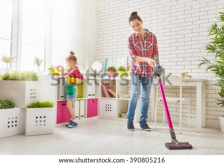 Happy family cleans the room. Mother and daughter do the cleaning in the house. A young woman and a little child girl wiped the dust and vacuumed the floor. - stock photo