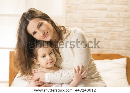Happy family concept. Mother and her little lovely daughter, concept of togetherness. Mother embracing her beautiful little girl while sitting on the bed at home - stock photo