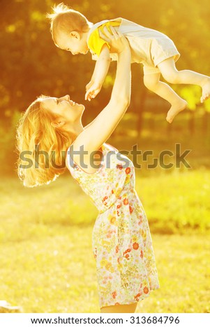 Happy family concept. Portrait of playing mother and little son in trendy summer clothing. Mommy tossing up toddler. Rays of light at summer sunrise. Outdoor shot - stock photo