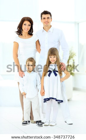 happy family consisting of mom dad doughterl and son looks at the camera and smiling - stock photo