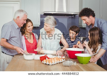Happy family cooking food on table in kitchen at home - stock photo