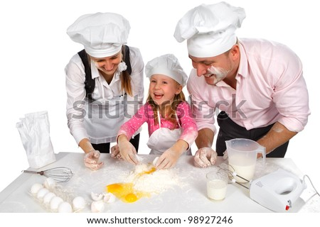 Happy family cooking  together in the kitchen while little girl adding eggs in the flour - stock photo