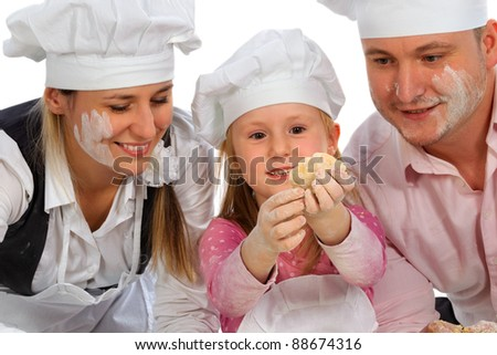 Happy family cooking  together in the kitchen while little girl making dumpling - stock photo