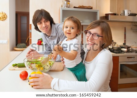 happy family couple with the baby in the kitchen