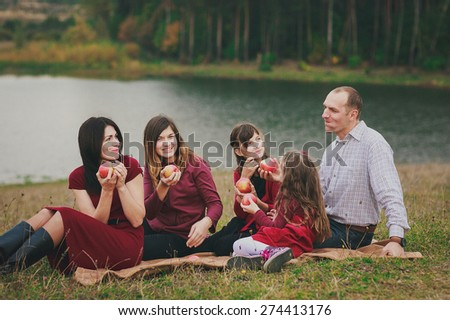 happy family couple with their three beautiful daughter eating big red apples by the lake - stock photo