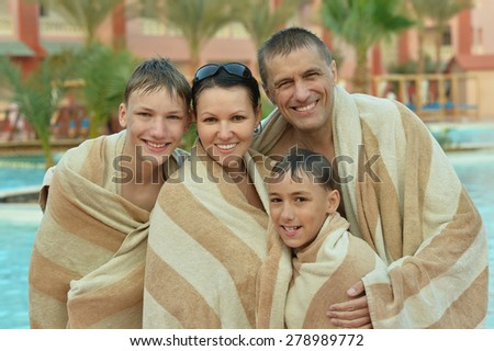 Happy family covered with towels near swimming pool - stock photo