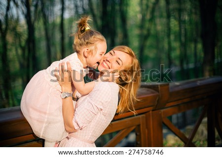 Happy family. Cute daughter kisses her mother while sitting at the bridge banister - stock photo