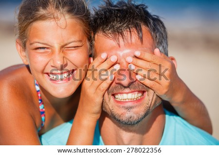 Happy family - Cute girl covers her dads eyes while playing at the beach - stock photo
