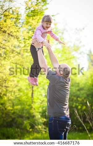 Happy family Dad throws child daughter up on a walk in the autumn leaf fall in park - stock photo