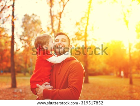 Happy family. daughter kissing and hugging her dad on a walk in the autumn leaf fall in park - stock photo