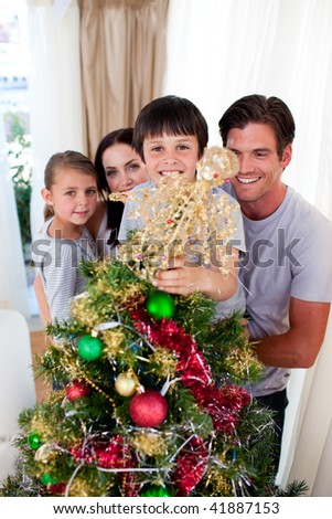 Happy family decorating a Christmas tree in the living-room - stock photo