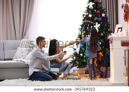 Happy family decorating Christmas tree in the room - stock photo