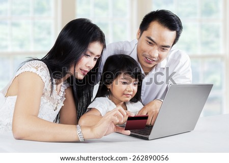 Happy family doing online payment by using a credit card and laptop computer at home - stock photo
