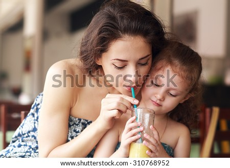Happy family drinking orange juice and joying together in urban cafe. Closeup natural emotion portrait - stock photo