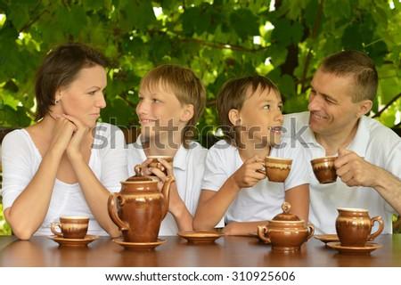 Happy family drinking tea in summer garden - stock photo