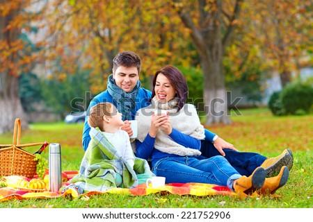 happy family drinking warm tea on autumn picnic - stock photo